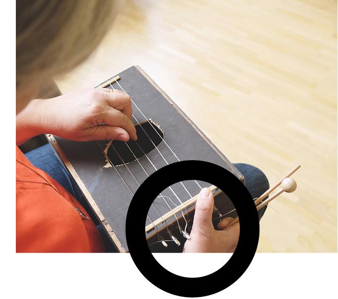 Judith Sonntag spielt ein selbstgebautes Zupfinstrument